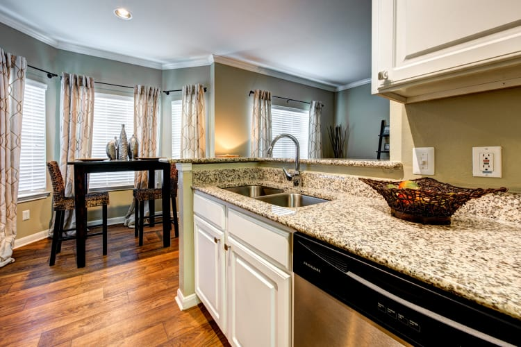 Renovated kitchen with granite countertops and hardwood flooring in a model home at Baypoint in Corpus Christi, Texas