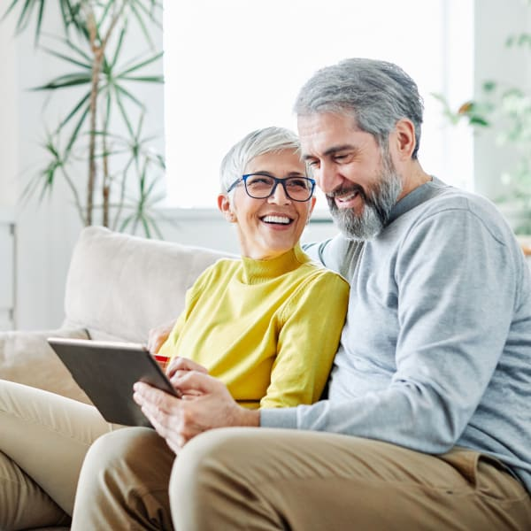A resident couple looking at photos of Pacifica Senior Living Menifee in Sun City, California.