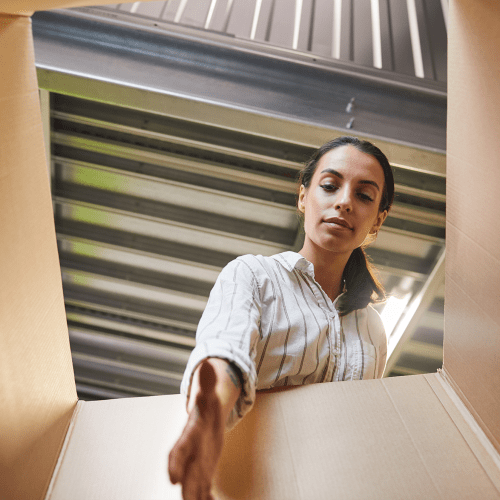 Woman reaching into box inside a climate-controlled unit at A-American Self Storage in Reno, Nevada