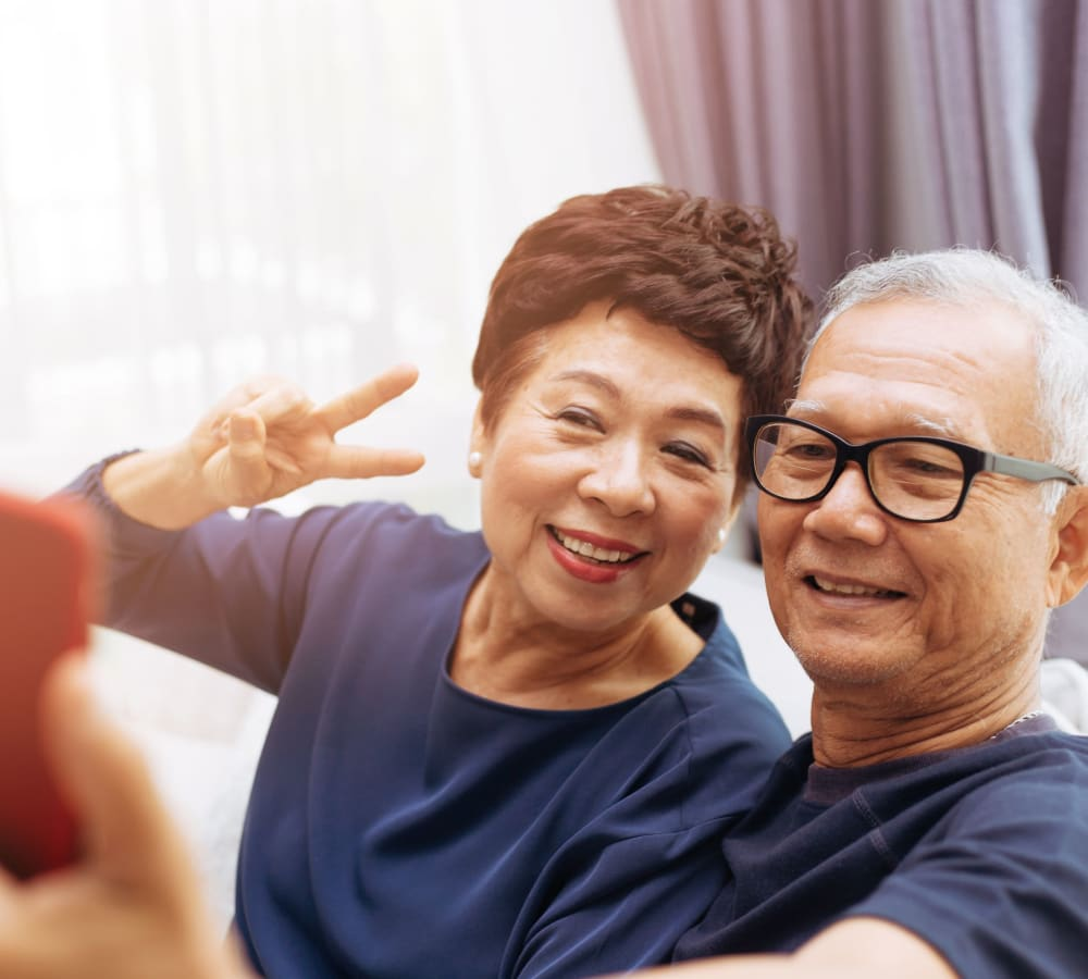Couple taking a photo together at Fairbrooke Senior Apartments in Aberdeen, Maryland