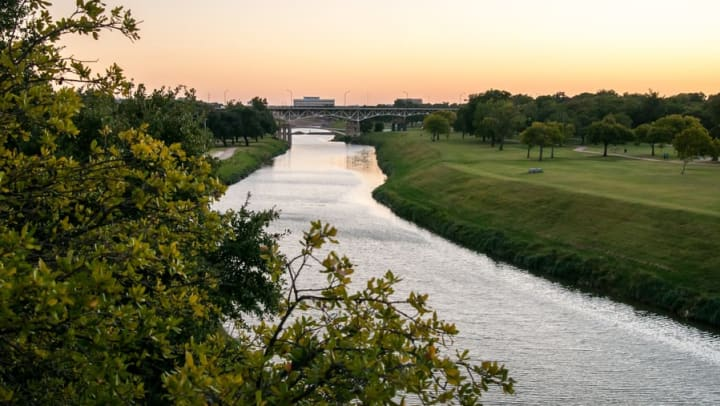 Local river and surrounding green parkland near Olympus 7th Street Station in Fort Worth, Texas