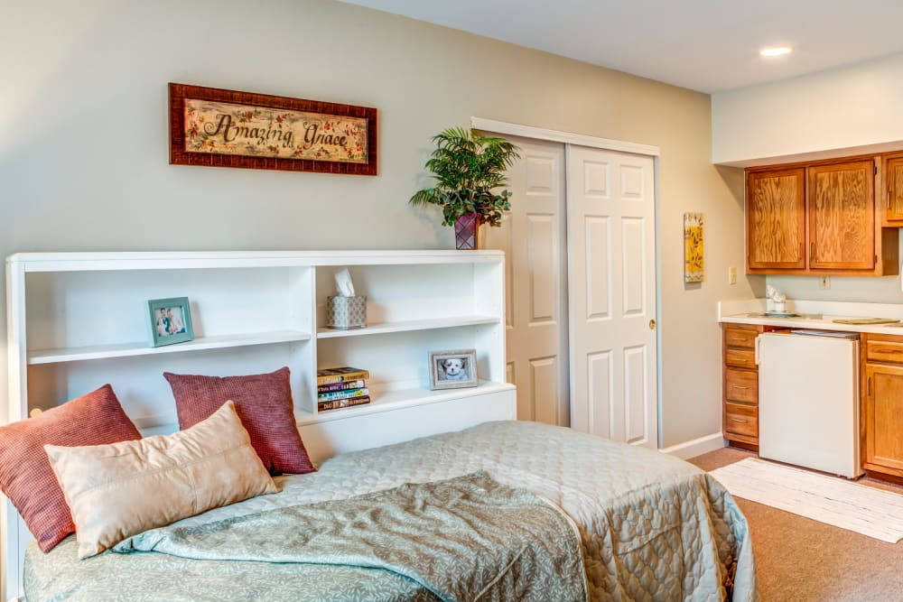 Brightly lit apartment with bed and kitchen with wood accents at Carriage Court of Lancaster in Lancaster, Ohio