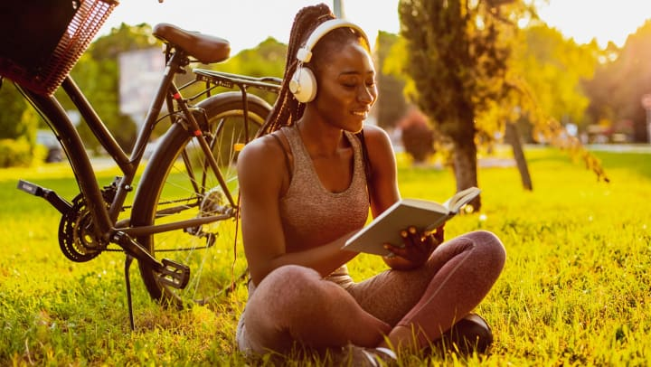 Young woman in athletic clothes wearing headphones and reading a book while sitting on the grass in a park next to a bicycle