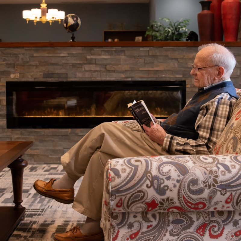 Resident sitting on a couch reading a newspaper in a large fireplace lounge at Aurora on France in Edina, Minnesota