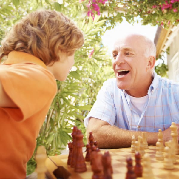 A man and his grandson playing chess at Pacifica Senior Living Sterling in Sterling, Virginia