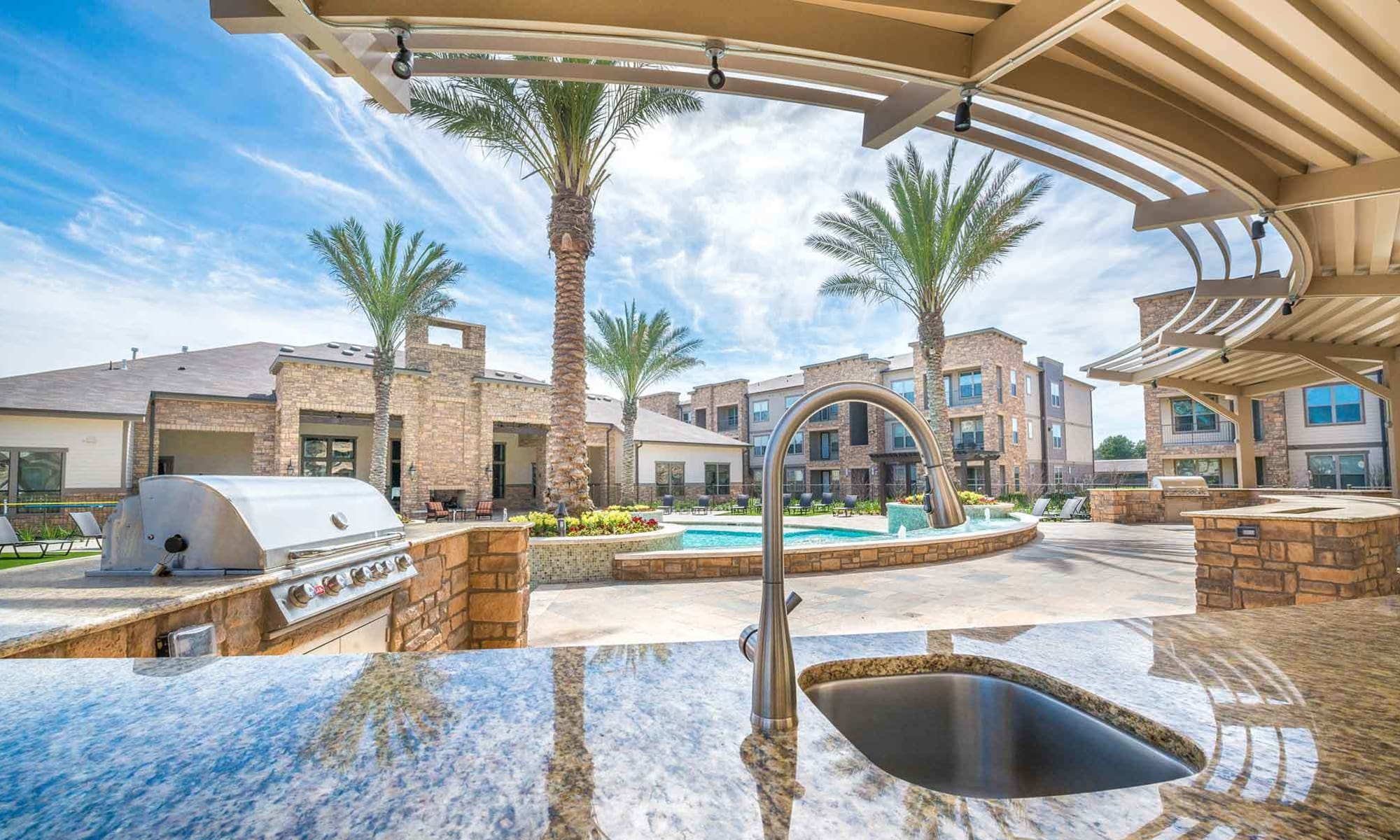 Outdoor kitchen, BBQ grills, and more outside near the swimming pool at The Abbey at Spring Town Center