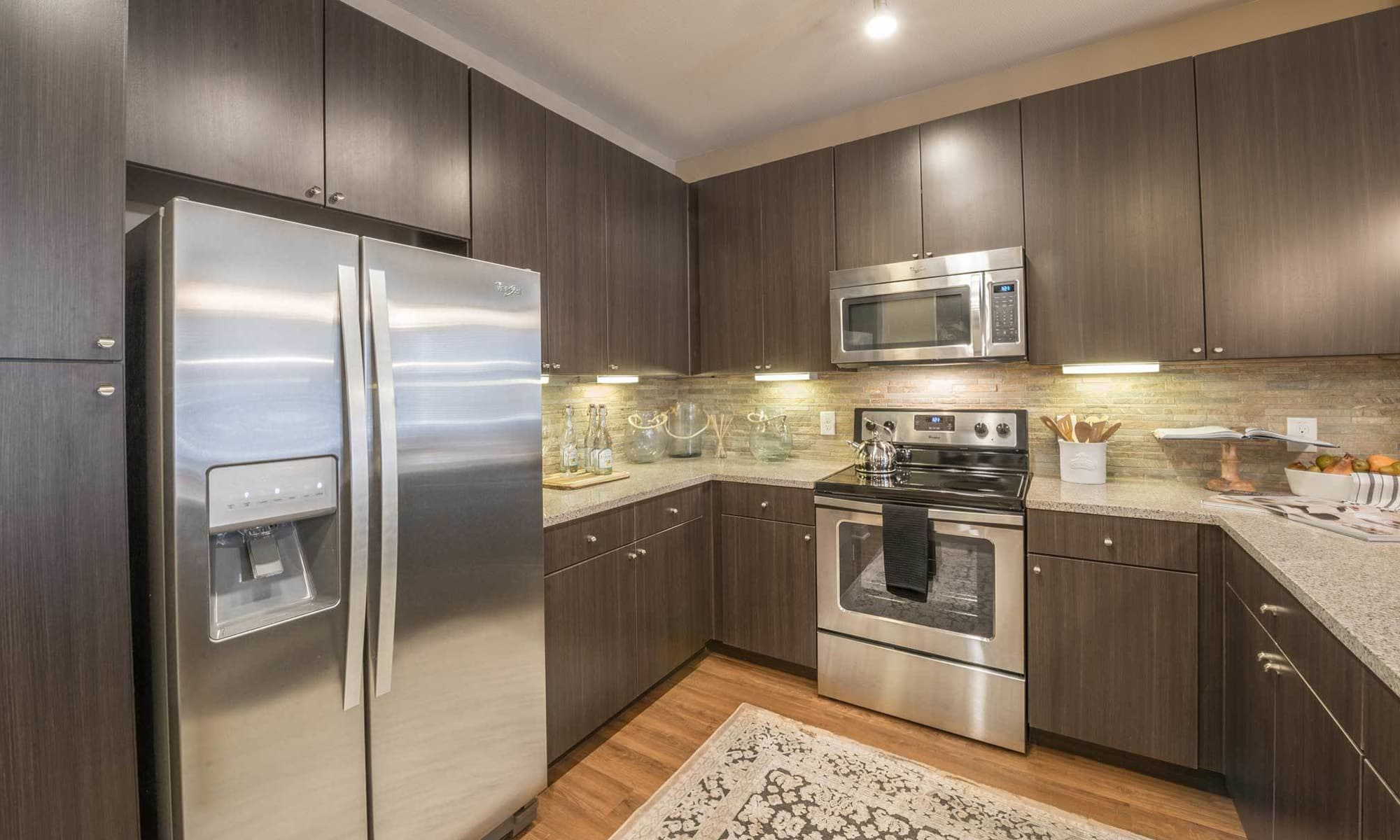 Dark wood cabinets and stainless-steel appliances in model kitchen at The Abbey at Spring Town Center