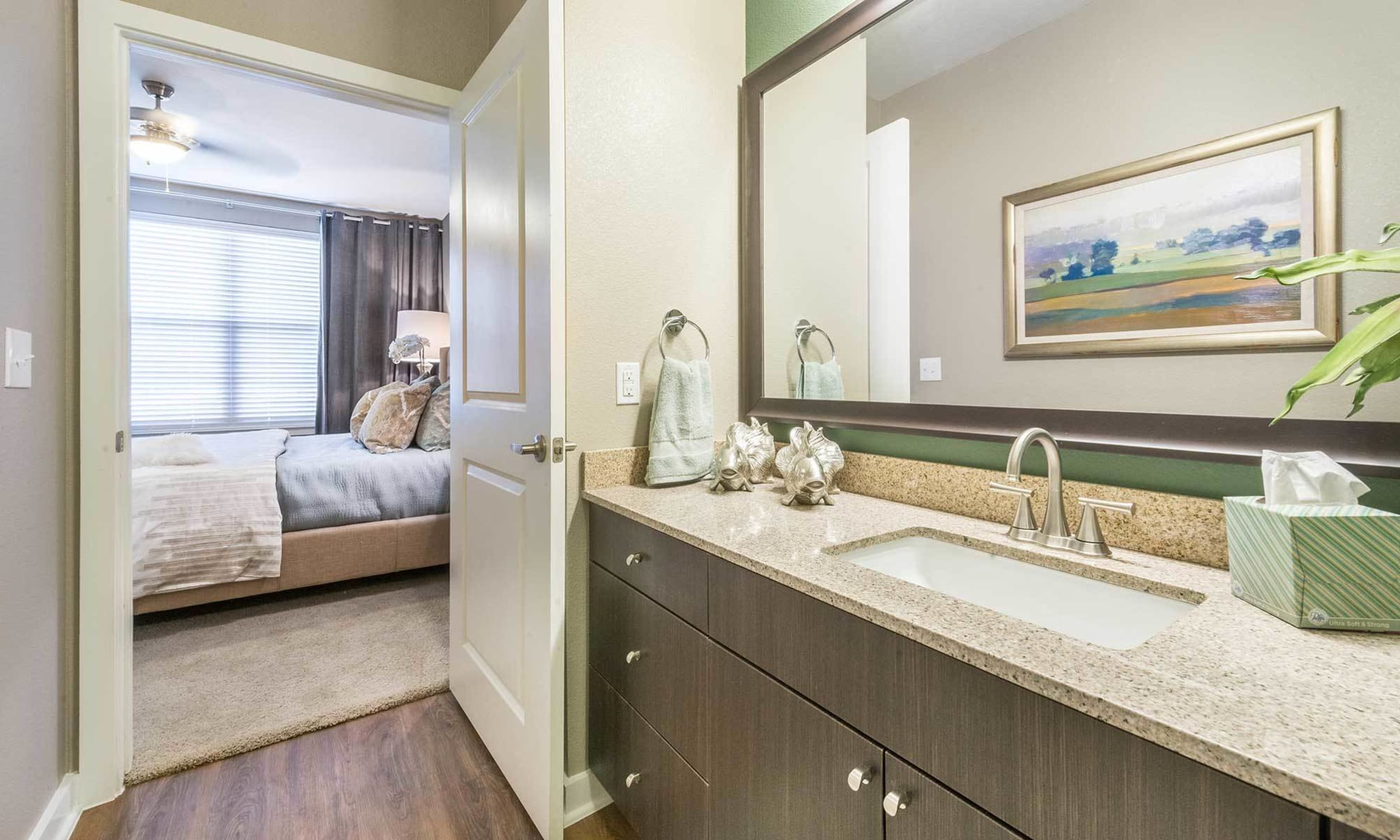 View of model apartment home's bedroom from luxurious master bath at The Abbey at Spring Town Center