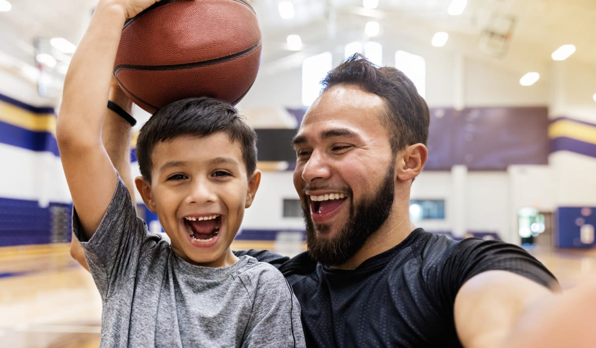 Father posing for a photo with his son after basketball practice near Rancho Los Feliz in Los Angeles, California