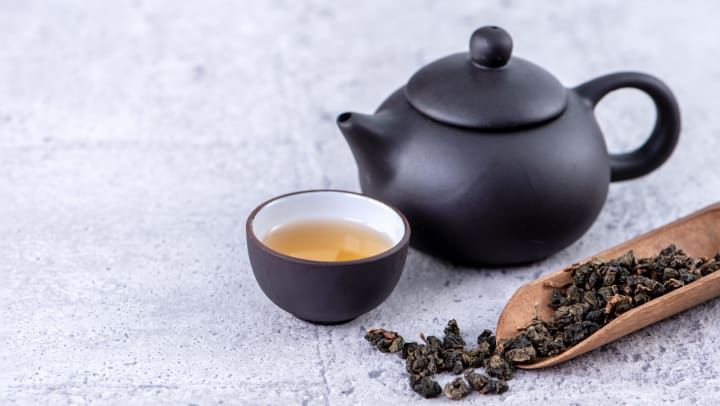 Hot tea in black teapot and cups and dry tea leaves over a bright gray cement background.