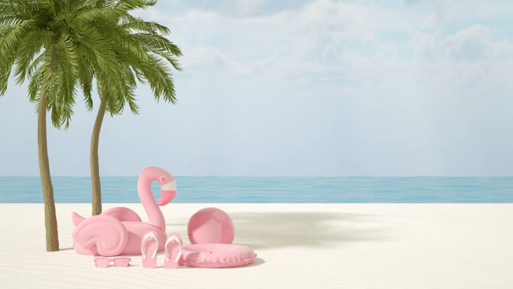 Several pink objects including an inflatable swan, beach ball, life preserver, flip flops and sunglasses on a beach with palm trees and the ocean in the background.