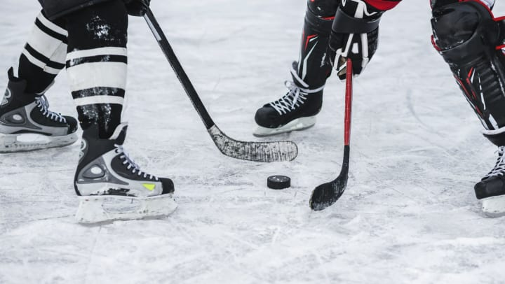 Close-up of a puck between two ice hockey players