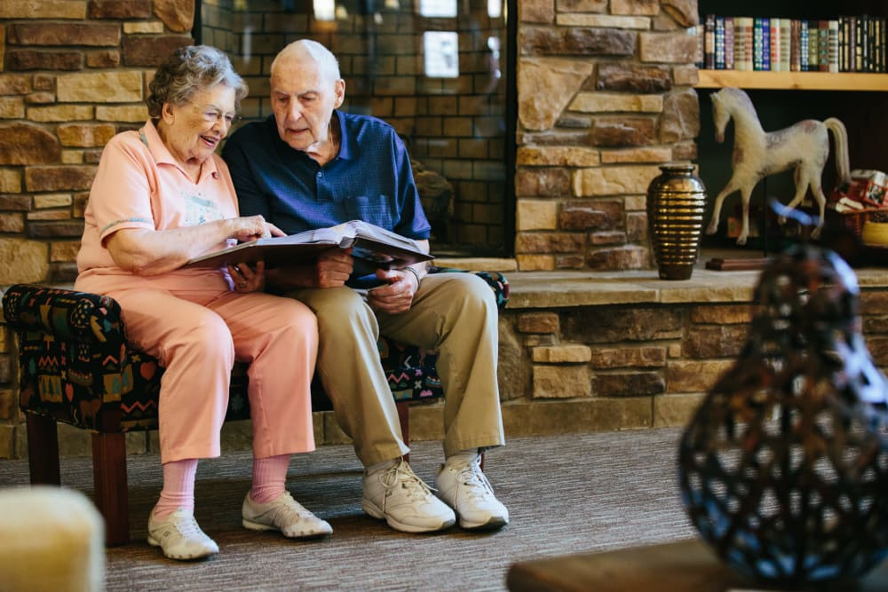 Two residents looking through a photo album together at The Springs at Missoula in Missoula, Montana.