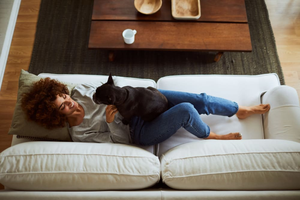 Resident relaxing on her couch with her dog at Bend at New Road Apartments in Waco, Texas