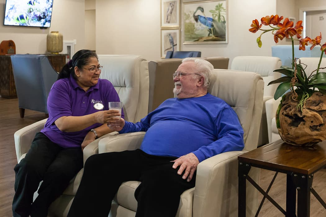 A resident and staff member getting to know each other in the Great Room at Iris Memory Care of Turtle Creek in Dallas, Texas.