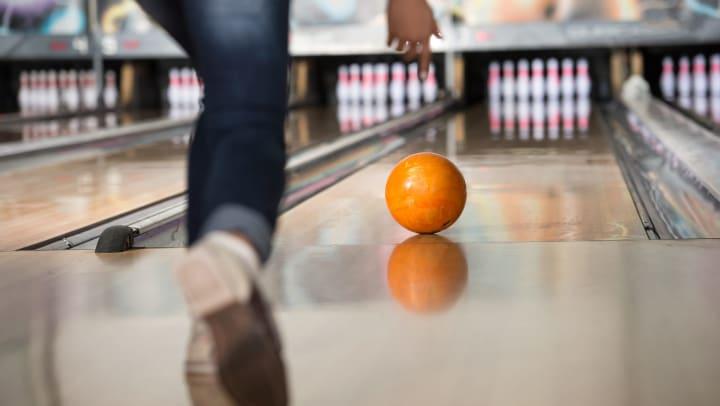 Bowler rolling bowl down bowling lane.