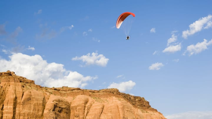 person paragliding in the sky over a desert landscape