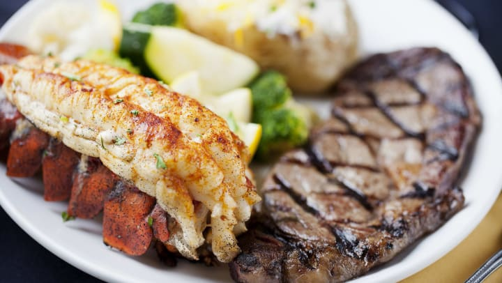 A plate with lobster tail, steak and a baked potato