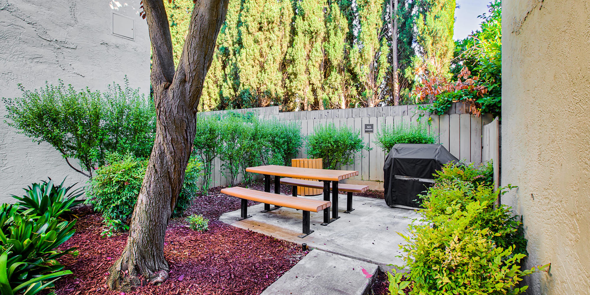 Barbecue area surrounded by lush landscaping at Pleasanton Place Apartment Homes in Pleasanton, California
