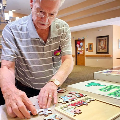 Resident doing a puzzle at Oxford Glen Memory Care at Sachse in Sachse, Texas