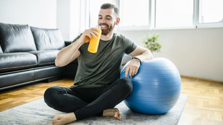 Young man wearing yoga pants and athletic shirt sitting on the floor of a sunlit apartment drinking orange electrolyte beverage and leaning on an exercise ball
