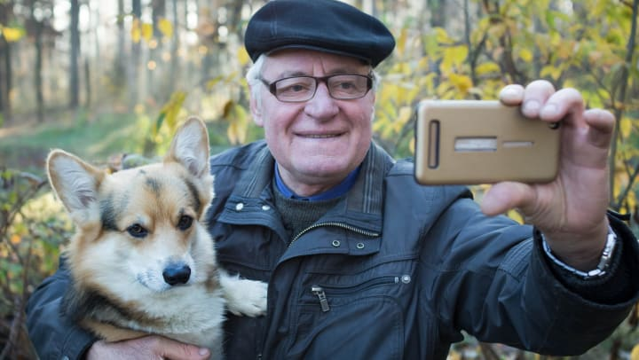 An older man holding a Corgi dog takes a selfie with his phone in the forest.