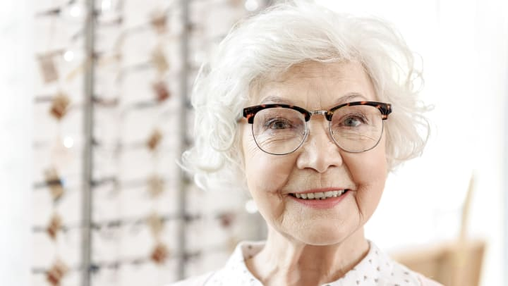A senior woman smiles in an eyewear store as she shows off a stylish pair of glasses to the person taking the picture.