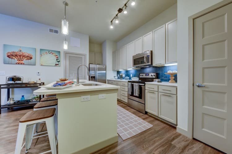 Granite countertops and antique-style cabinetry in a model home's kitchen at Agave in San Antonio, Texas