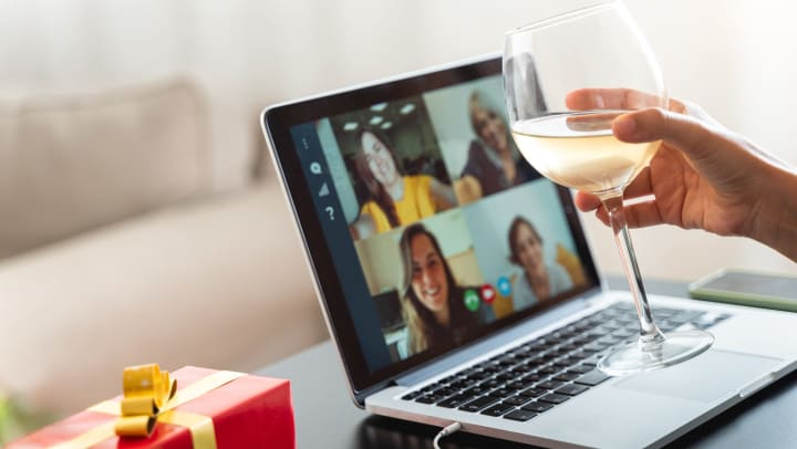 A woman's hand with a glass of wine in front of a computer with four other women on the screen.