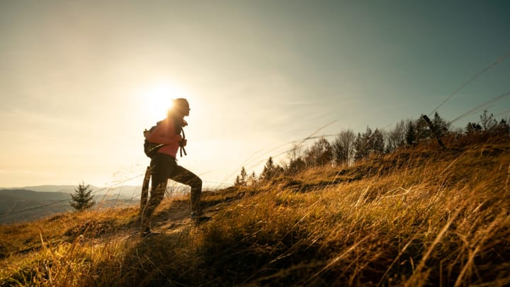Silhouette of woman wearing backpack hiking on mountain