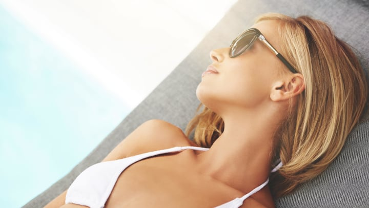 Woman in a white bikini and sunglasses lounging by the pool
