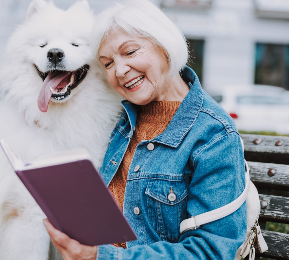 Resident and her dog reading at Bridgeport Place Assisted Living in University Place, Washington.
