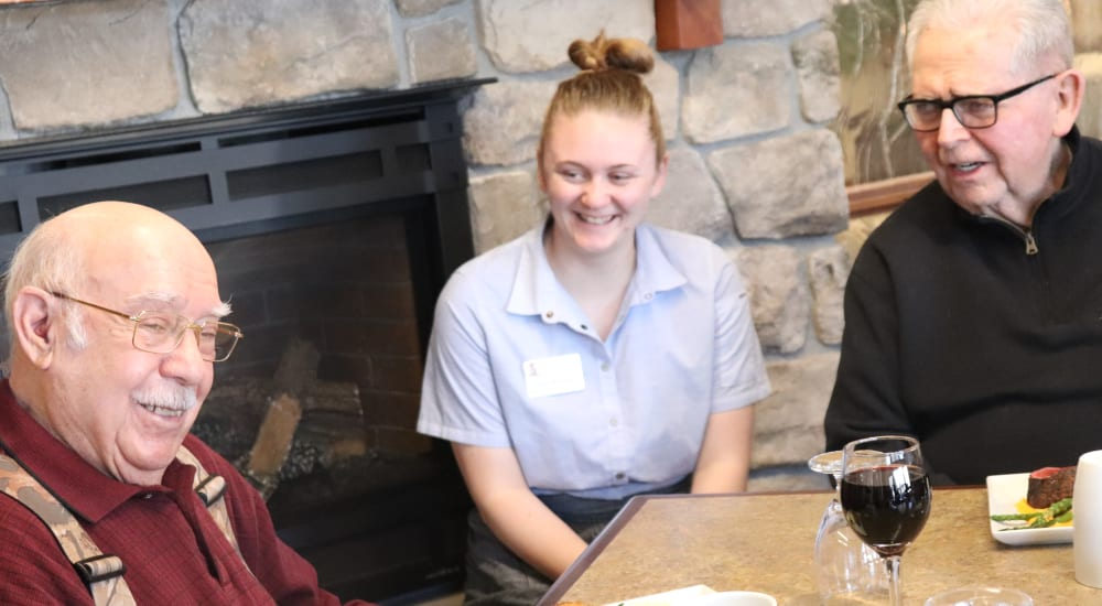 Two residents dining with a caregiver at The Springs at Butte in Butte, Montana