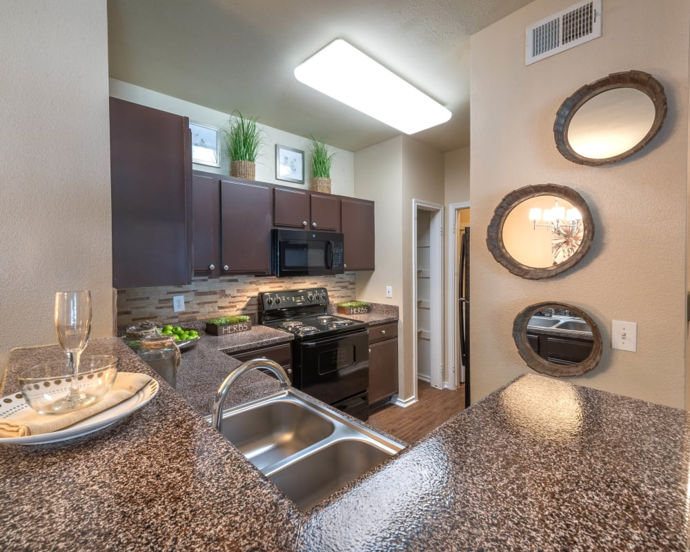 Gourmet kitchen with beautiful granite countertops in a model home at The Ranch at Shadow Lake in Houston, Texas