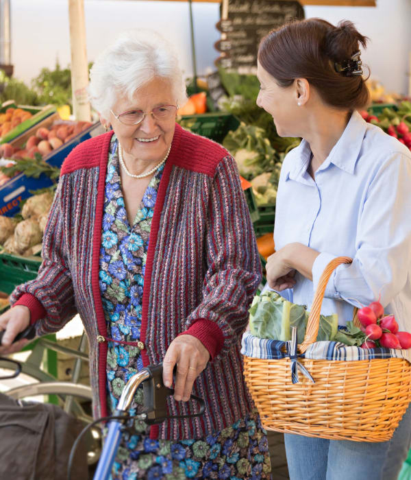 Resident at caretaker shopping at the grocery store near at The Phoenix at Lake Joy in Warner Robins, Georgia