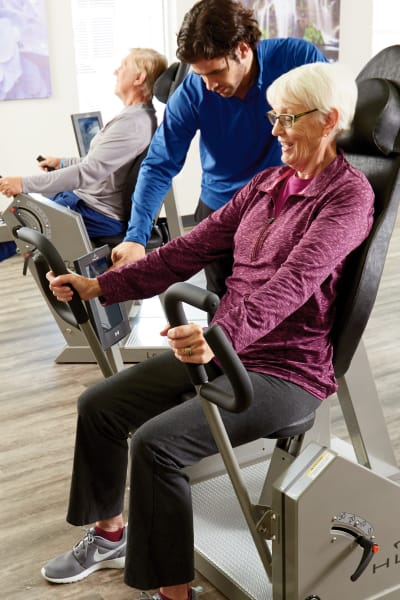 Gym instructor assisting a resident on a workout machine at Quail Park at Browns Point in Tacoma, Washington