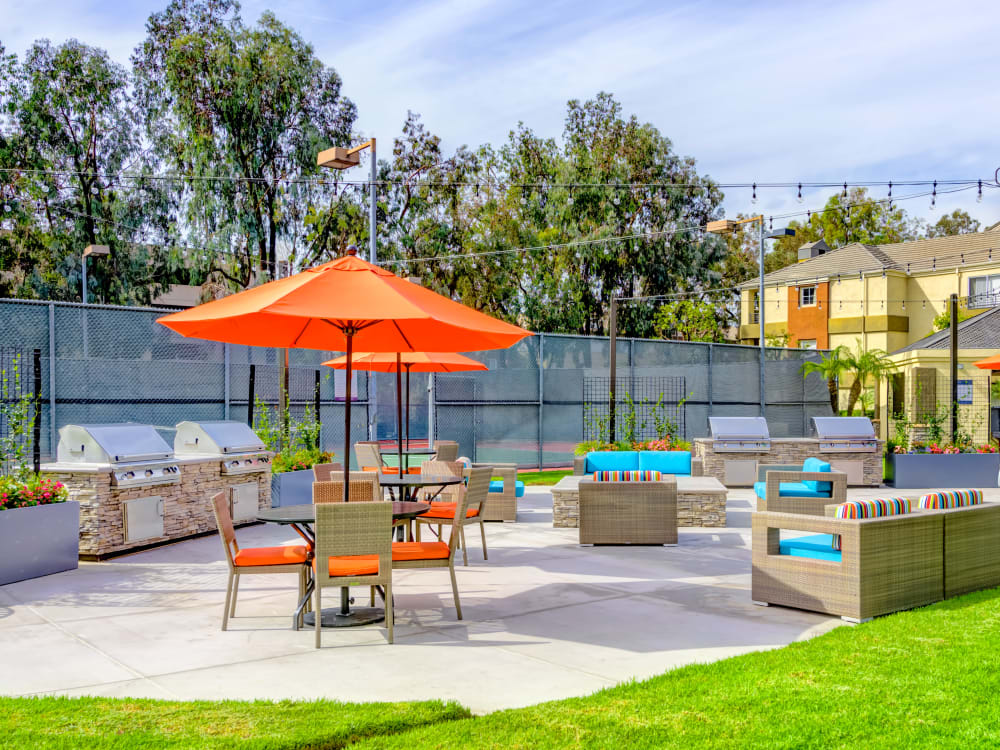 Barbecue area with a fire pit and lounge seating at Sofi Irvine in Irvine, California
