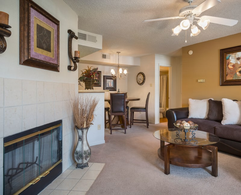 Comfortably decorated living area with a fireplace and an accent wall in a model home at The Mansion in Independence, Missouri