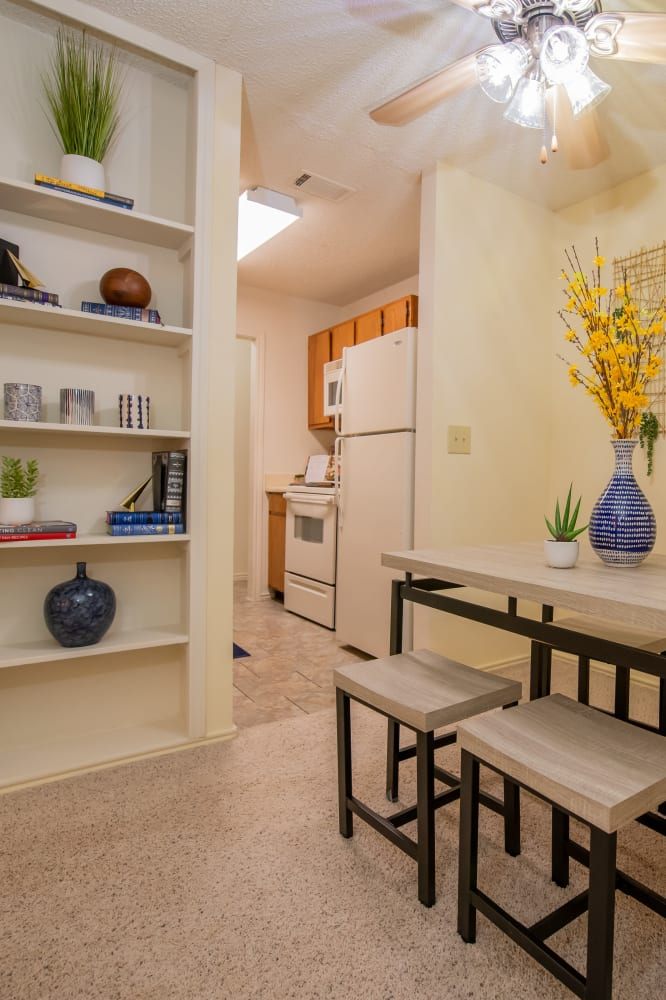 Dining room with built-in shelves and kitchen at Newport Apartments in Amarillo, Texas