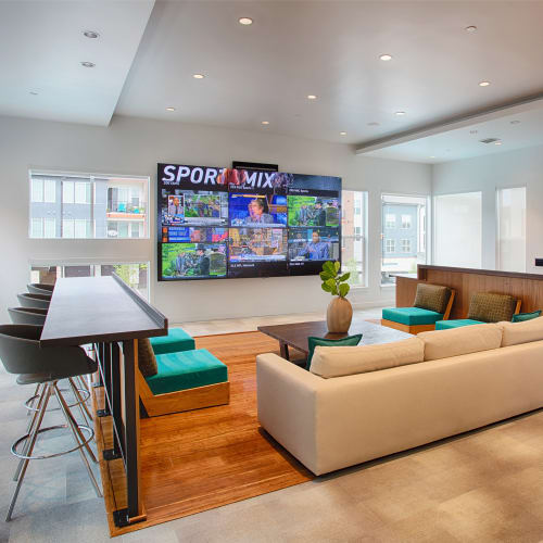 A big tv and comfy couch seating in the resident lounge at Elevate in Englewood, Colorado