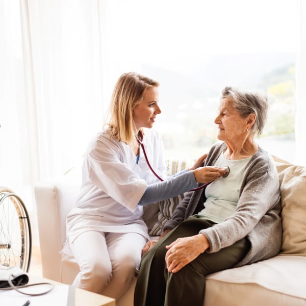 Onsite nurse listening to the heartbeat of a resident at Quail Park on Cypress in Visalia, California
