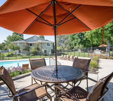 Outdoor table and chairs shaded by an umbrella at Ridgecrest Apartment Homes in Martinez, California