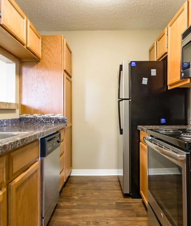 Model kitchen with stainless-steel appliances, granite countertops, and hardwood floor at North Pointe Apartments