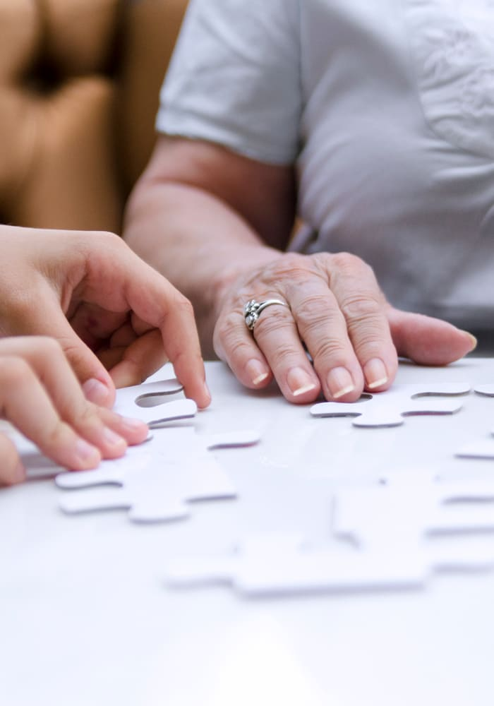 A caregiver and resident put together a puzzle at Lighthouse Memory Care in Anacortes, Washington