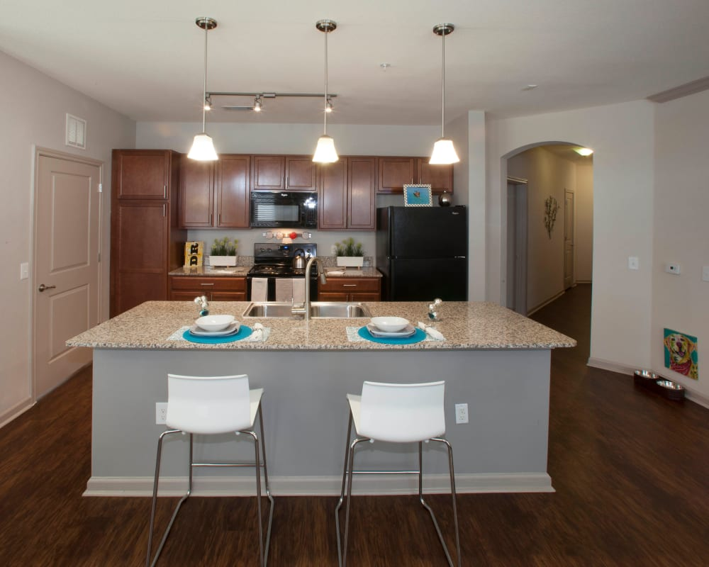 Open-concept model home's kitchen with hardwood floors and breakfast bar at Olympus Katy Ranch in Katy, Texas