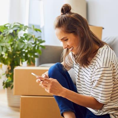Woman looking at her phone near A-American Self Storage in Santa Fe Springs, California