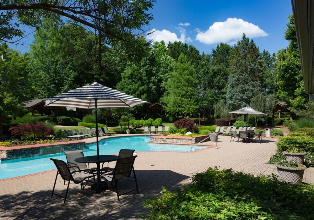 Lush mature trees providing shade at the resort-style swimming pool area at The Vinings at Newnan Lakes in Newnan, Georgia