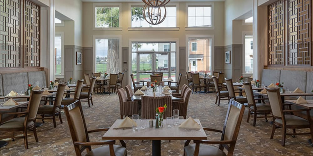 Resident dining room with beautiful modern chandelier at The Springs at Sherwood in Sherwood, Oregon