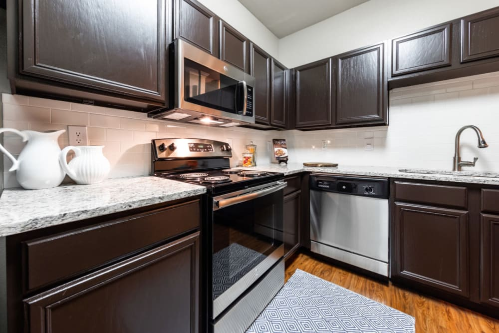 Kitchen with wood style flooring at Marquis at Ladera Vista in Austin, Texas