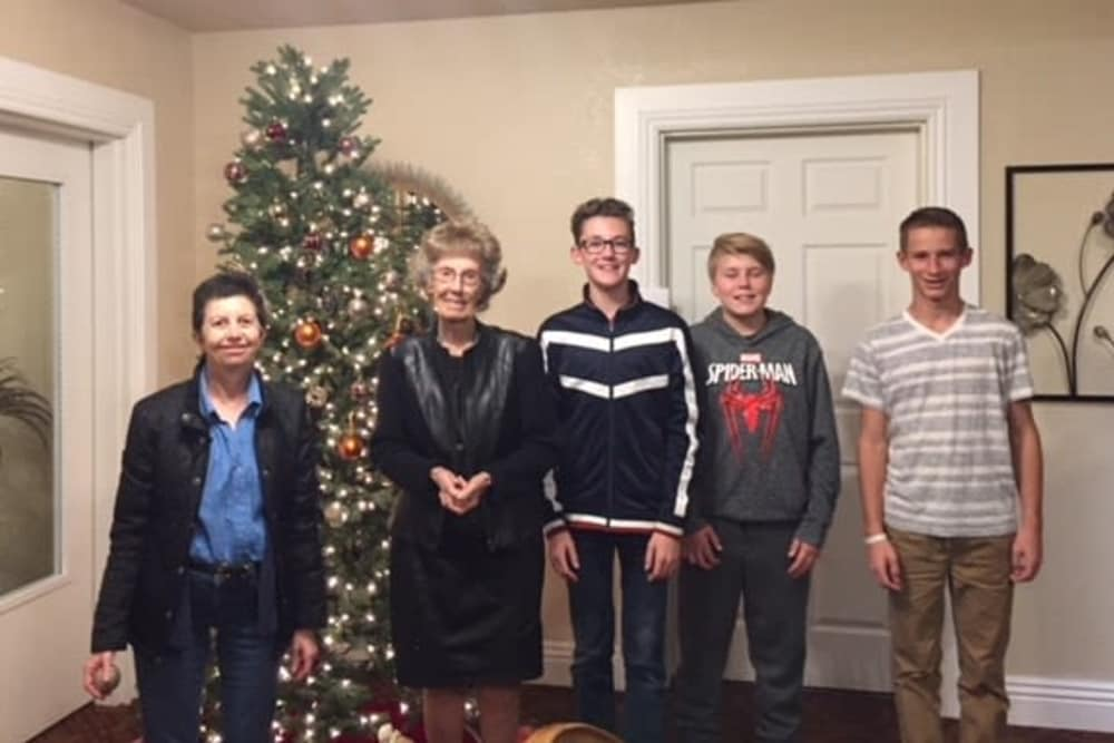 senior resident and family in front of Christmas tree